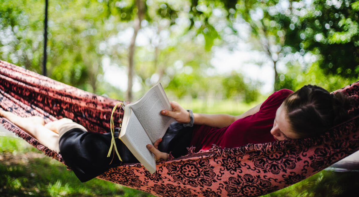 Reading outside in a hammock under the trees